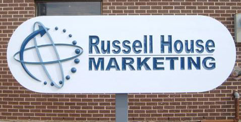 Russell House Marketing  Clear western red cedar with incised V-carved text and raised sculptural accents.