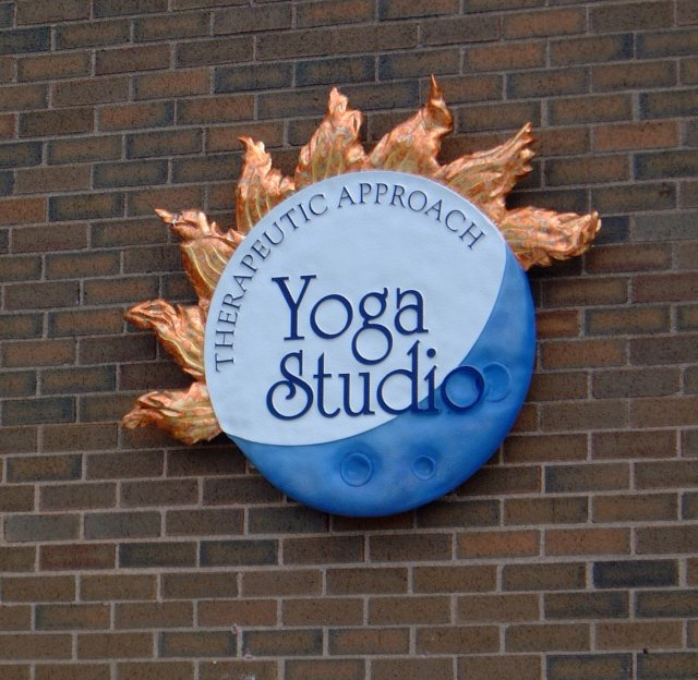 Yoga Studio Sculptural reproduction of Yoga Studio's logo. 3' wide this is a combination of sandblast and carved HDU. Finished with custom mixed paints and variegated copper leaf accents.